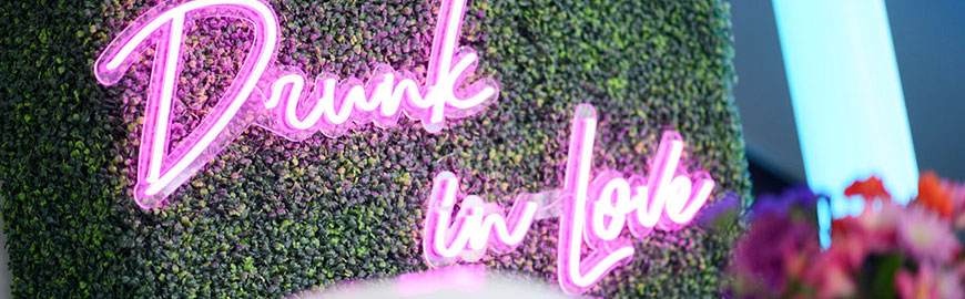 """Boxwood Hedge with """"Drunk in Love"""" pink neon sign"""